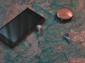 A phone, headphones, and compass set on top of a map.